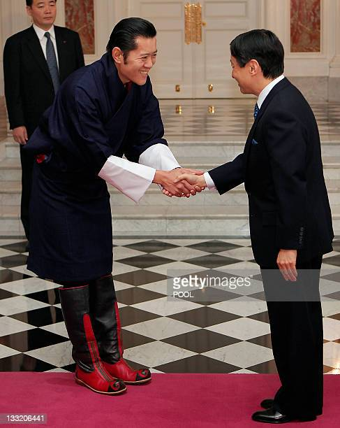 Japan's Crown Prince Naruhito shakes hands with Bhutan's King Jigme Khesar Namgyel Wangchuck during a visit to their guest house in Tokyo on November...