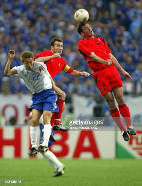 Japan's Daisuke Ichikawa , Belgium's team captain and forward Marc Wilmots and midfielder Bart Goor are airborne during match 13 group H of the 2002...