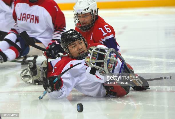 Japan's Daisuke Uehara and Norway's Knut Andre Nordstoga fight for the puck in the ice hockey classification game between Norway and Japan at the...