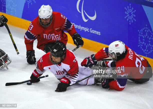 Japan's Daisuke Uehara and Norway's Thommas Avdal fight for the puck during the ice hockey classification game between Norway and Japan at the...