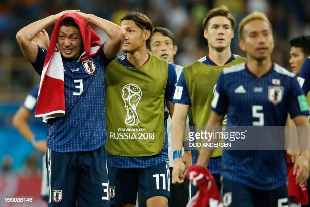 Japan's defender Gen Shoji and Japan's forward Takashi Usami look dejected at the end of the Russia 2018 World Cup round of 16 football match between...