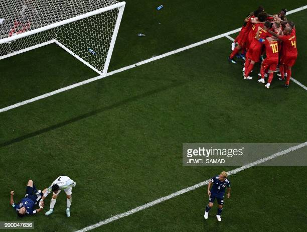 Japan's defender Gen Shoji Japan's goalkeeper Eiji Kawashima and Japan's defender Yuto Nagatomo react as Belgium's players celebrate their winning...