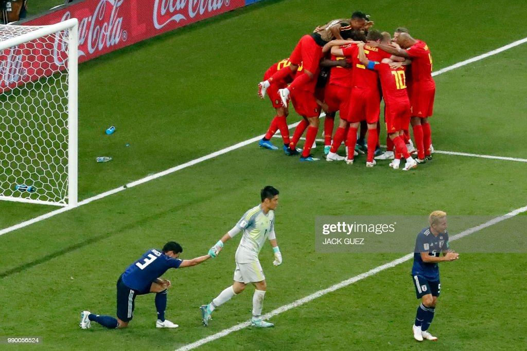 Japan's defender Gen Shoji (L), Japan's goalkeeper Eiji Kawashima (C) and Japan's defender Yuto Nagatomo (R) react as Belgium's players celebrate their winning goal during the Russia 2018 World Cup round of 16 football match between Belgium and Japan at the Rostov Arena in Rostov-On-Don on July 2, 2018. (Photo by Jack GUEZ / AFP) / RESTRICTED