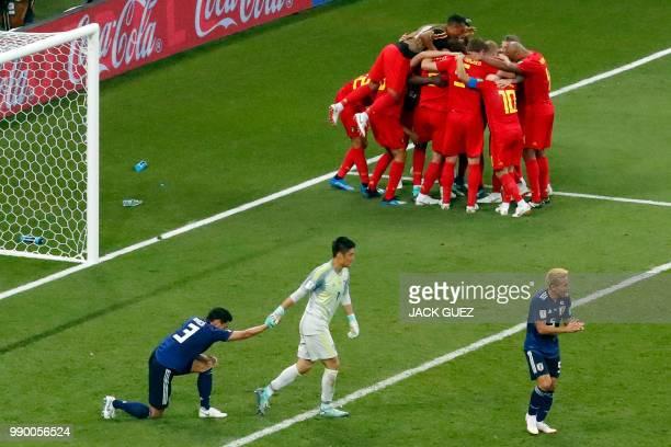 Japan's defender Gen Shoji Japan's goalkeeper Eiji Kawashima and Japan's defender Yuto Nagatomo react as Belgium's players celebrate their winning...