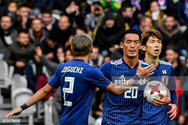 Japan's defender Makino Tomoaki celebrates with teammates after scoring a goal during the friendly football match between Japan and Brazil on...