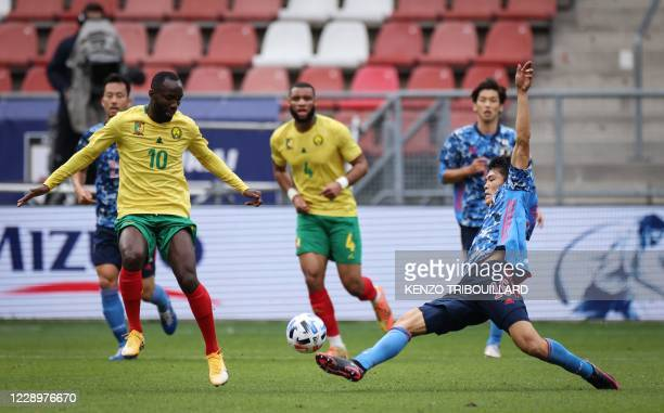 Japan's defender Takehiro Tomiyasu fights for the ball with Cameroon's forward Moumi Ngamaleu during a friendly football match between Japan and...