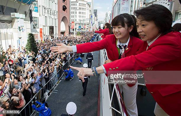 Japan's delegation chief Seiko Hashimoto right speaks with Ai Fukuhara second from right as they stand on the top of a double decker bus during the...