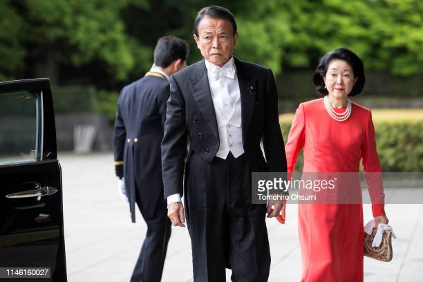 Japan's Deputy Prime Minister and Finance Minister Taro Aso and his wife Chikako arrive for Emperor Naruhito's ceremony for inheriting the Imperial...