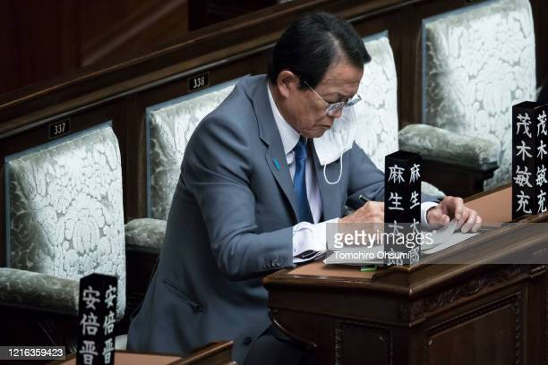 Japan's Deputy Prime Minister and Finance Minister Taro Aso wearing a face mask attends an ordinary session at the upper house of parliament on April...