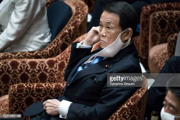 Japan's Deputy Prime Minister and Finance Minister Taro Aso wearing a face mask attends a budget committee meeting at the lower house of parliament...