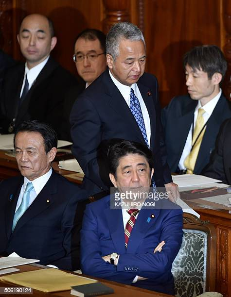 Japan's Economy and Fiscal Policy Minister Akira Amari walks behind Prime Minister Shinzo Abe and Finance Minister Taro Aso to deliver his policy...