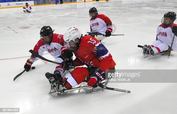Japan's Eiji Misawa and Norway's Emil Sorheim fight for the puck during the ice hockey classification game between Norway and Japan at the Gangneung...