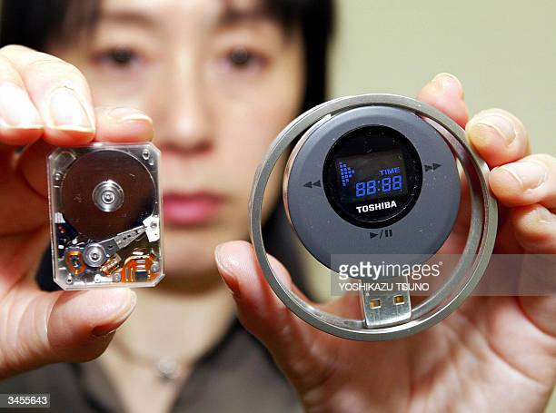 Japan's electronics giant Toshiba employee Junko Furuta displays prototype model of the hard disk audio player equipped with world's smallest 085inch...