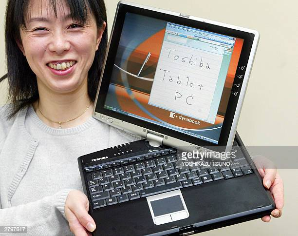Japan's electronics giant Toshiba employee Junko Furuta displays the new tablet PC dynabook SS M200 equipped with 14GHz Intel's Pentium M processor...