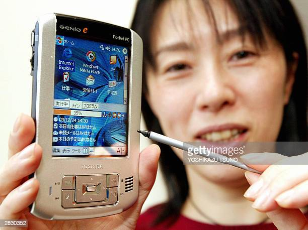 Japan's electronics giant Toshiba employee Junko Furuta displays the thin and light PDA Genio e400 equipped with Intel's 300MHzPXA263 processor on...