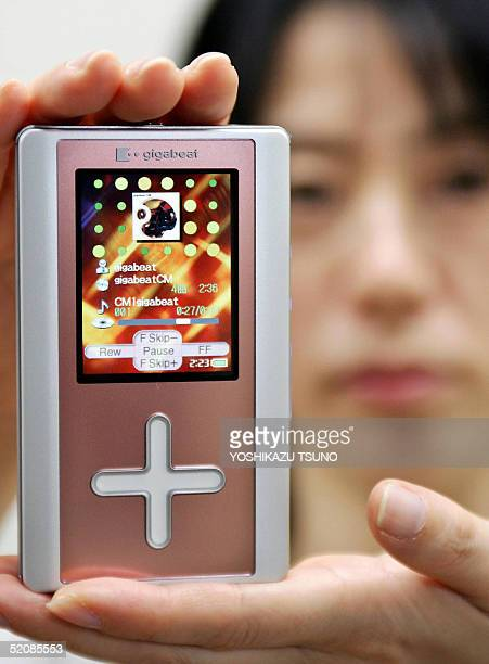 Japan's electronics giant Toshiba employee Junko Furuta displays the company's latest audio player gigabeat F60 equipped with a 60GB harddisk...