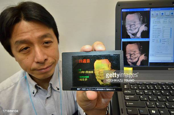 Japan's electronics maker Pioneer engineer Takanori Tateoka displays a hologram of a sevenmonth fetus face at the baby and kids expo in Tokyo on June...