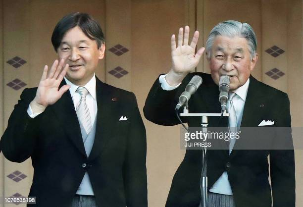 Japan's Emperor Akihito and Crown Prince Naruhito wave to the crowd during the New Year's greeting ceremony at the Imperial Palace in Tokyo on...