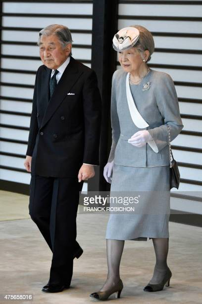 Japan's Emperor Akihito and Empress Michiko walk on their way to welcome Philippine President Benigno Aquino at the Imperial Palace in Tokyo on June...