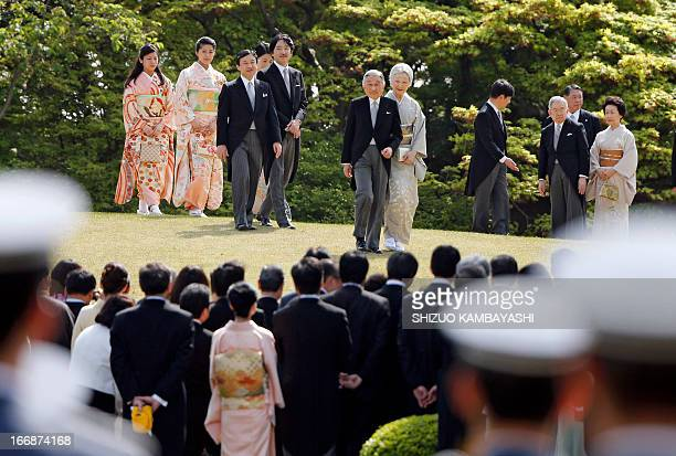 Japan's Emperor Akihito and Empress Michiko walk to a crowd of guests during the annual spring garden party at the Akasaka Palace imperial garden in...