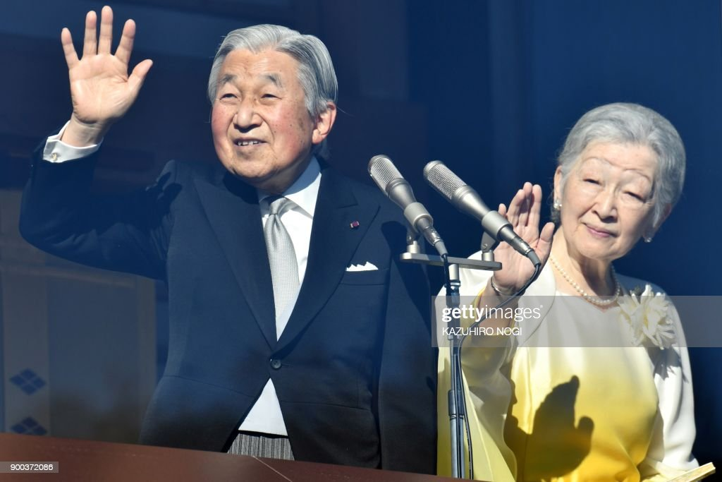 Japan's Emperor Akihito and Empress Michiko wave to well-wishers from the balcony of the Imperial Palace in Tokyo on January 2, 2018. / AFP PHOTO / Kazuhiro NOGI
