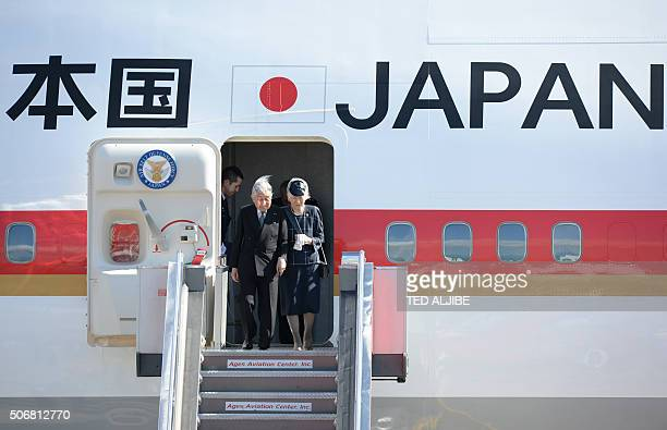 Japan's Emperor Akihito and his wife Empress Michiko acknowledge well wishers as they prepare to disembark from a plane shortly after arriving at the...