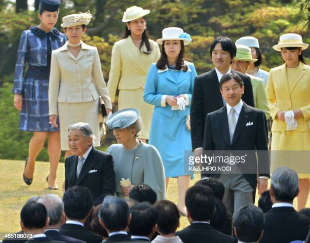 Japan's Emperor Akihito Empress Michiko and the imperial family members walk towards a crowd of guests during the annual spring garden party at the...
