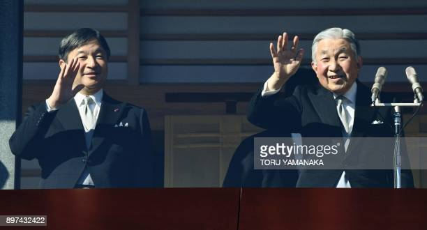Japan's Emperor Akihito waves to wellwishers beside his son Crown Prince Naruhito from a balcony at the Imperial Palace in Tokyo on December 23 2017...