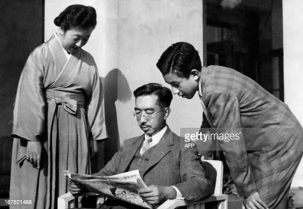 Japan's Emperor Hirohito reads a newspaper while Empress Kojun and Crown Prince Akihito looks on at the Royal Palace in Tokyo in the 1950th Akihito...