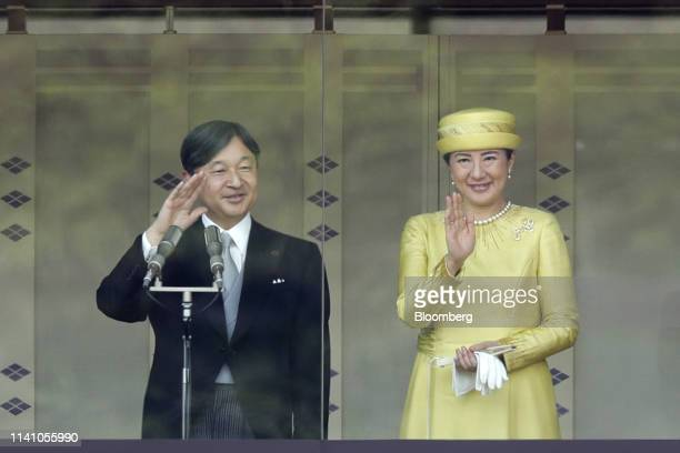 Japan's Emperor Naruhito left and Empress Masako wave to members of the public during a greeting ceremony at the Imperial Palace in Tokyo Japan on...