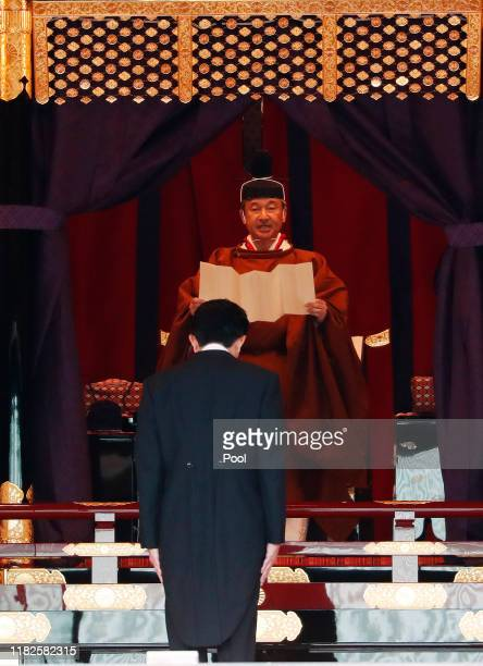 Japan's Emperor Naruhito speaks as Prime Minister Shinzo Abe is seen during a ceremony to proclaim his enthronement to the world, called...