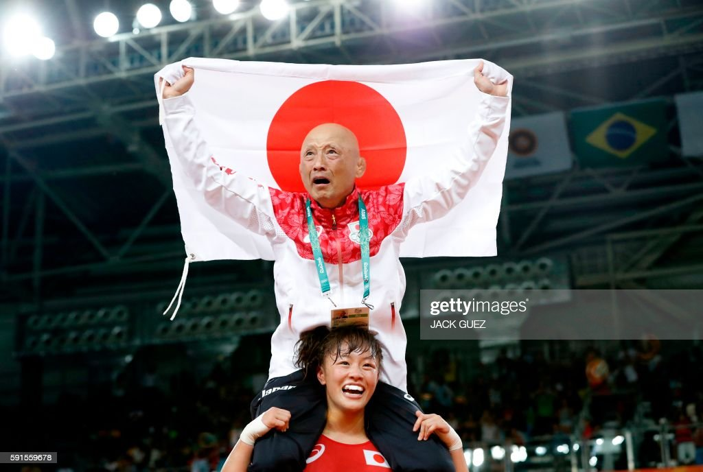 TOPSHOT - Japan's Eri Tosaka celebrates with her coach winning against Azerbaijan's Mariya Stadnyk in their women's 48kg freestyle final match on August 17, 2016, during the wrestling event of the Rio 2016 Olympic Games at the Carioca Arena 2 in Rio de Janeiro. / AFP / Jack GUEZ