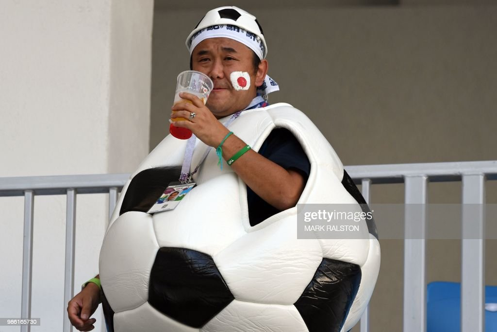 A Japan's fan disguised as a giant football drinks as he waits before the Russia 2018 World Cup Group H football match between Japan and Poland at the Volgograd Arena in Volgograd on June 28, 2018. (Photo by Mark RALSTON / AFP) / RESTRICTED
