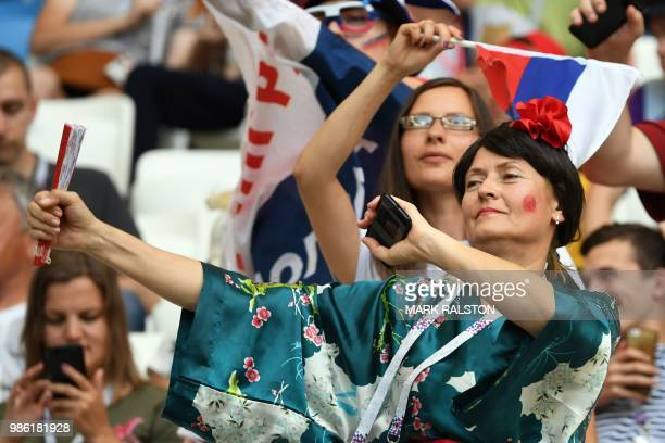 A Japan's fan wearing a kimono gestures during the Russia 2018 World Cup Group H football match between Japan and Poland at the Volgograd Arena in...