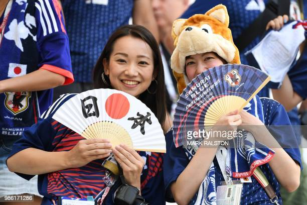 Japan's fans pose with their fans before the Russia 2018 World Cup Group H football match between Japan and Poland at the Volgograd Arena in...