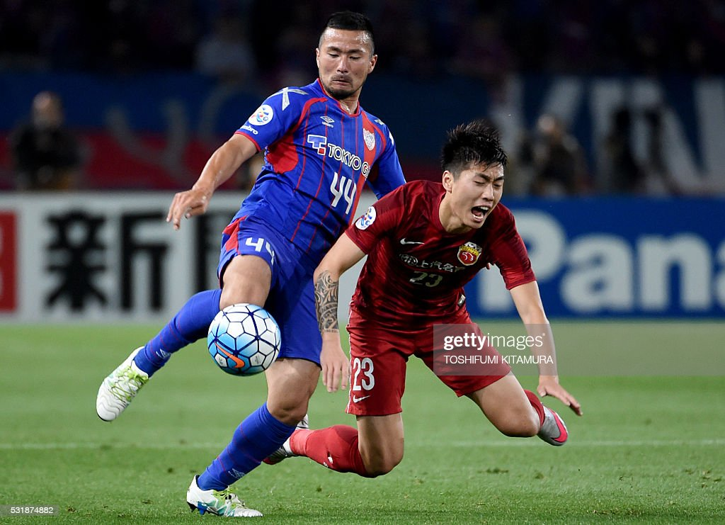 Japan's FC Tokyo forward Takuma Abe (L) fights for the ball with China's Shanghai SPIG defender Fu Huan (R) during the AFC champions league round of 16 first match in Tokyo on May 17, 2016. / AFP / TOSHIFUMI
