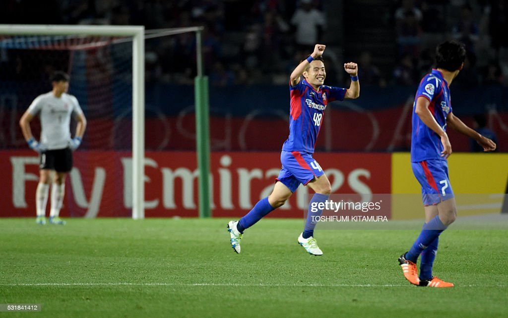 Japan's FC Tokyo midfielder Kota Mizunuma (C) celebrates his goal beside midfielder Takuji Yonemoto (R) during the AFC champions league round of 16 first match against China's Shanghai SPIG in Tokyo on May 17, 2016. / AFP / TOSHIFUMI