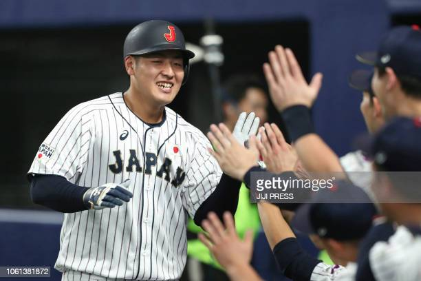 Japan's first baseman Kazuma Okamoto celebrates his home run with teammates during the second inning of the fifth exhibition baseball game between...
