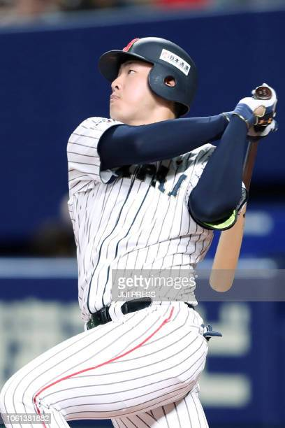 Japan's first baseman Kazuma Okamoto hits a home run during the second inning of the fifth exhibition baseball game between the US Major League...