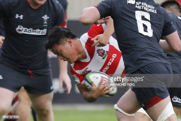Japan's flanker Hisanobu Okayama is tackled during the U20 World Rugby union Championship match between Wales and Japan at the Aime Giral stadium on...