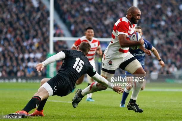 Japan's flanker Michael Leitch evades a tackle from England's fullback Elliot Daly as he runs to the line to score a try during the international...