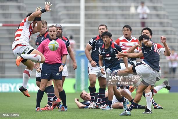 Japan's fly half Ryoto Nakamura blocks the ball kicked by Hong Kong's fly half Benjamin Rimene during their Asia Rugby Championship match at the...