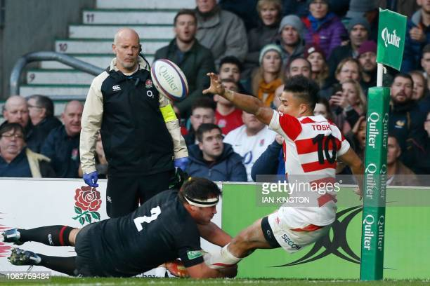 Japan's flyhalf Yu Tamura is pushed into touch by England's hooker Jamie George to save a try during the international rugby union test match between...