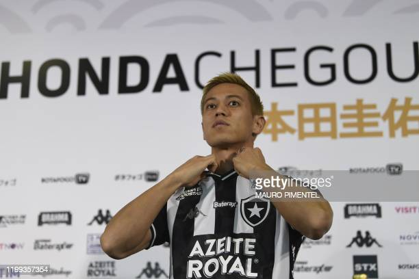 Japan`s footballer Keisuke Honda puts on his new Brazil's Botafogo jersey during the press conference of his official presentation at in Rio de...