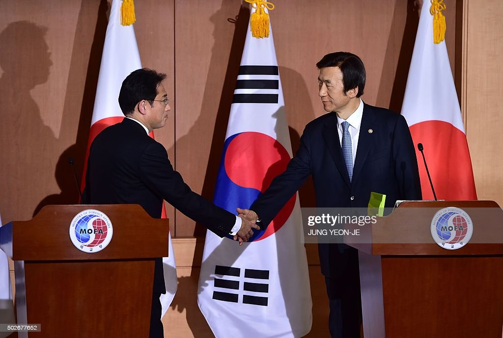 Japan's Foreign Minister Fumio Kishida (L) shakes hands with his South Korean counterpart Yun Byung-Se (R) after a joint press briefing at the Foreign Ministry in Seoul on December 28, 2015. South Korea and Japan reached a landmark agreement on the thorny issue of wartime sex slaves that has long strained relations, Seoul's foreign minister said.