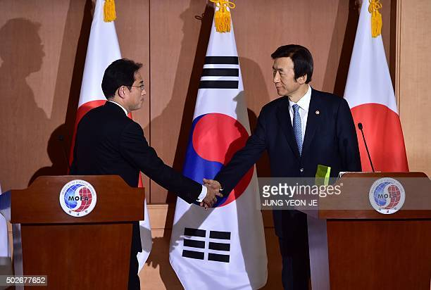 Japan's Foreign Minister Fumio Kishida shakes hands with his South Korean counterpart Yun ByungSe after a joint press briefing at the Foreign...