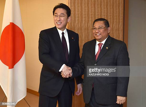 Japan's Foreign Minister Fumio Kishida shakes hands with Myanmar's Foreign Minister Wunna Maung Lwin during his visit to the Foreign Ministry in...