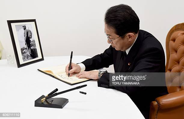 Japan's Foreign Minister Fumio Kishida writes a message in a condolence book in front of a portrait of the late Cuban revolutionary icon Fidel Castro...