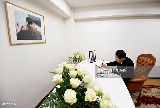 Japan's Foreign Minister Fumio Kishida writes a message in a condolence book in front of portraits of the late Cuban revolutionary icon Fidel Castro...
