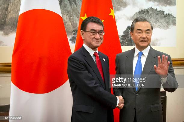 Japan's Foreign Minister Taro Kono shakes hands with China's Foreign Minister Wang Yi as he arrives for a meeting at the Diaoyutai State Guesthouse...